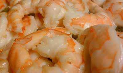 Buttery, garlicky shrimp await some chives. Photo: CC--David Murray